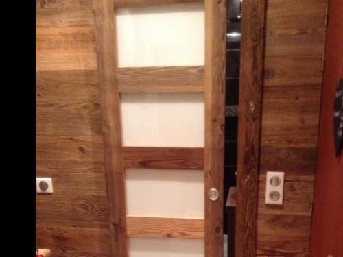 Porte coulissante en vieux bois et vitres blanches laquées